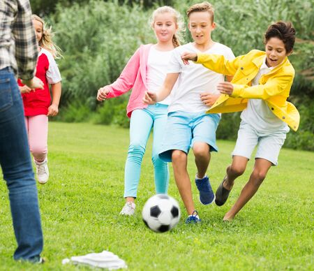 Photo pour Cheerful happy children are jogning and playing football in the park. - image libre de droit
