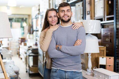 Photo pour Portrait of attractive girl and her boyfriend in antique furnishings store - image libre de droit