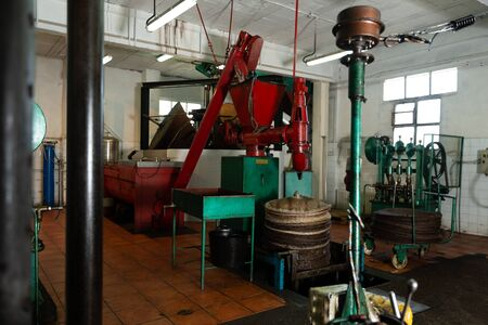 Photo pour Interior of small olive oil producing factory with machine for applying olive paste on fiber mats for pressing - image libre de droit