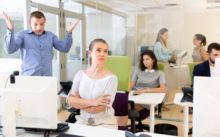 Photo pour Upset  girl sitting at laptop in coworking space while dissatisfied unhappy angry businessman pointing out mistakes in her work - image libre de droit