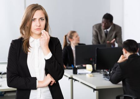 Photo for Portrait of upset young woman foreground in busy open plan office - Royalty Free Image
