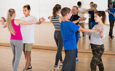 Photo pour Couples of young people having dancing partner dance in classroom - image libre de droit