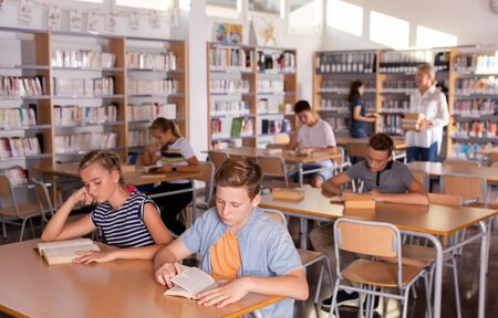 Teenage boys and girls preparing for exam in school library