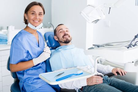 Photo pour Man is sitting satisfied in chair after treatment in dental office - image libre de droit