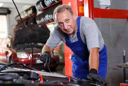 Elderly man mechanic engaged in car repair in modern auto workshop