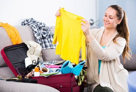 Young glad woman getting ready for vacations indoors