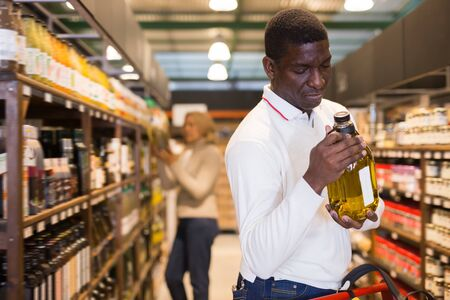 Photo pour Adult African American man making purchases in store, choosing vegetable oil - image libre de droit