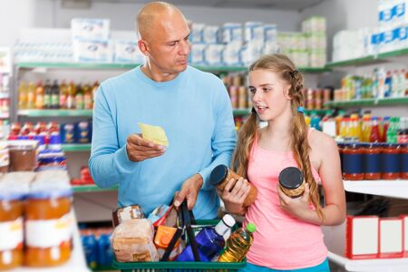 Photo for adult father doing shopping with preteen girl in food department of supermarket - Royalty Free Image