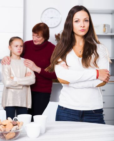 Photo pour Portrait of upset woman on background with her mother and daughter after quarrel - image libre de droit
