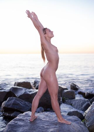Foto de Young nude female is standing on a rock near the sea at the dawn. - Imagen libre de derechos