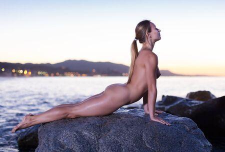 Foto de Nude young positive woman is lying on a rock near the sea at the dawn. - Imagen libre de derechos