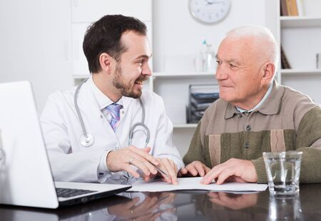 Photo for Elderly man comes to doctor in clinic for advice on health - Royalty Free Image