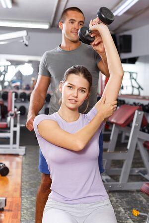 Photo pour Sporty man coaching girl and explaining exercises technique with dumbbells at gym - image libre de droit