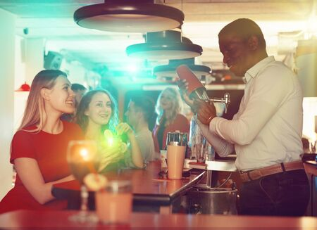 Photo pour Young women drink cocktails at the bar in nightclub - image libre de droit
