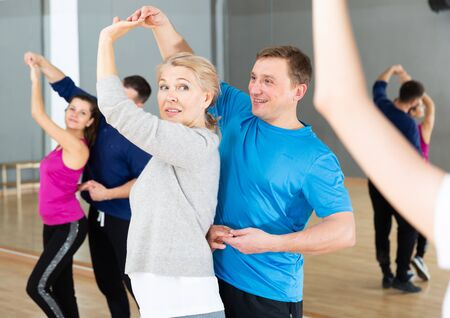 Photo pour Positive mature woman learning to dance kizomba with partner in dancing class - image libre de droit