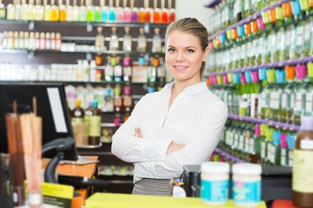 Photo pour Successful happy young saleswoman standing in perfume store - image libre de droit