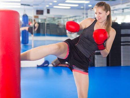 Photo pour Positive female is doing foot-kick in box gym - image libre de droit