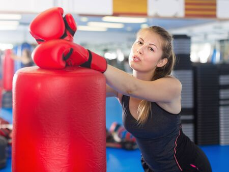 Photo pour Portrait of active woman standing with punching bag in box gym - image libre de droit