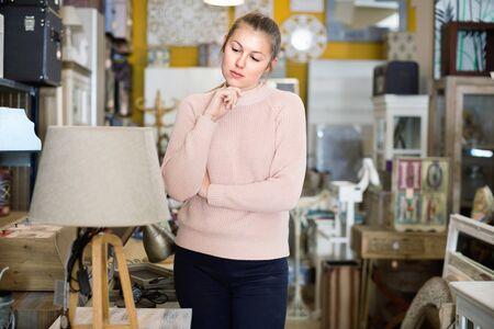 Photo pour positive woman buyer standing in furniture shop choosing modern torchere indoors - image libre de droit