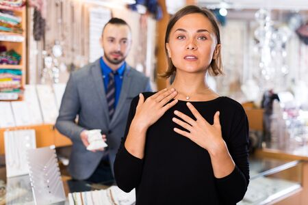 Photo pour Adult buyer woman choosing chainlet and pendants in the jewelry store - image libre de droit