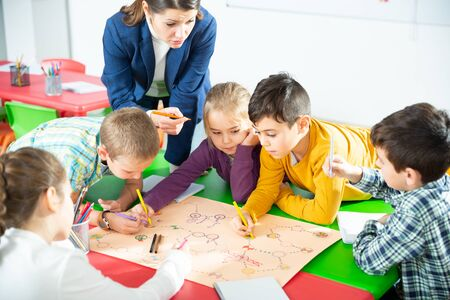 Photo pour Teacher and collective of elementary age children draw together a board game - image libre de droit