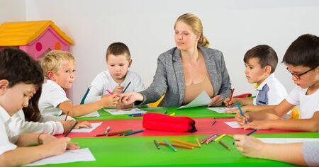 Friendly female teacher talking to children, sitting together around desk in classroom