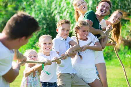 Photo for Happy  children with parents playing active games in summer park, tugging war - Royalty Free Image