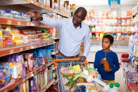 Foto für Happy friendly  pleasant  African family of father and tween son shopping together in supermarket - Lizenzfreies Bild