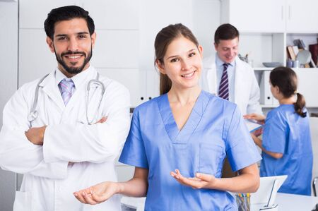 Photo pour Portrait of young female doctor with male colleague inviting in clinic - image libre de droit