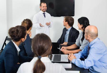 Photo pour Positive efficient scientist presenting report during working meeting in office - image libre de droit