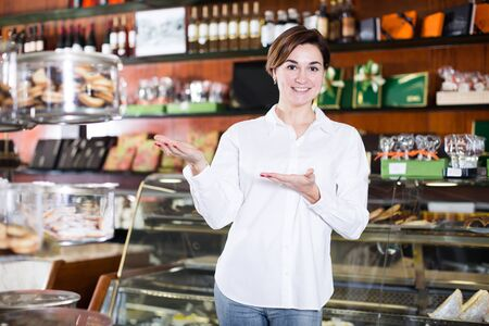 Photo pour Young woman seller displaying assortment of confectionery - image libre de droit