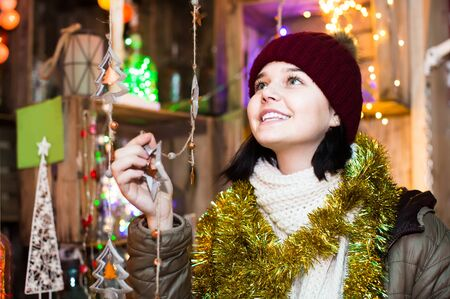 Photo for Beautiful young spanish girl choosing Christmas decoration at market - Royalty Free Image