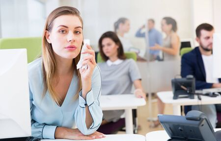 Photo pour Portrait of upset young woman foreground in busy open plan office - image libre de droit