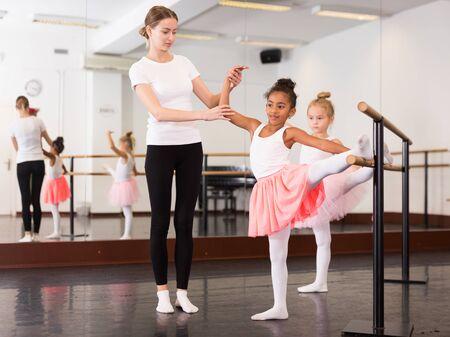 Photo pour Female ballet trainer teaching two little girls near ballet barre in dancing hall - image libre de droit