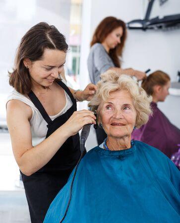 Foto de Friendly woman stylist performing hair styling with electric hair curler for senior lady in salon - Imagen libre de derechos