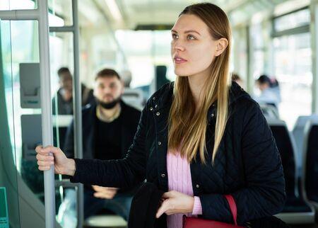 Photo pour Portrait of positive young woman traveling by modern city bus on sunny autumn day - image libre de droit