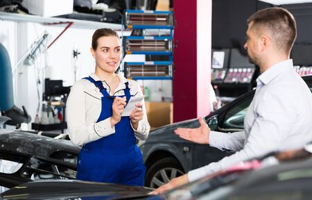 Professional female mechanic discussing with male client and recording list of works on car repair in auto repair shop