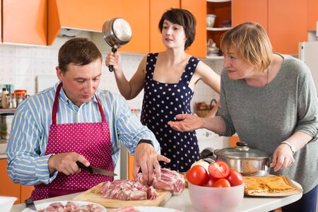 Photo for Senior and adult women scolding man cutting meat on wooden board in kitchen - Royalty Free Image
