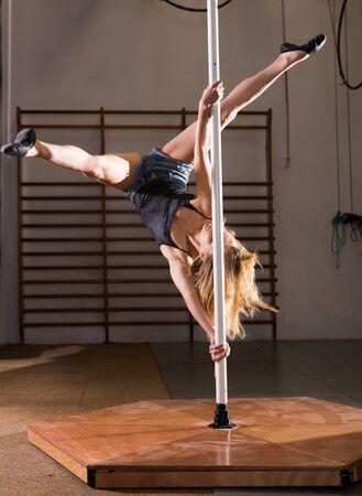 Photo pour Sexy girl in denim shorts performs a dance with a pylon - image libre de droit
