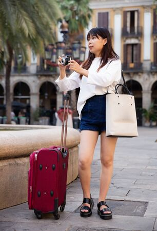 Photo for Young chinese woman traveler strolling with luggage around city, making photo of sights - Royalty Free Image