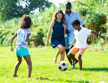 Photo pour Young mixed race parents with children having fun together outdoors, playing football on green grass - image libre de droit