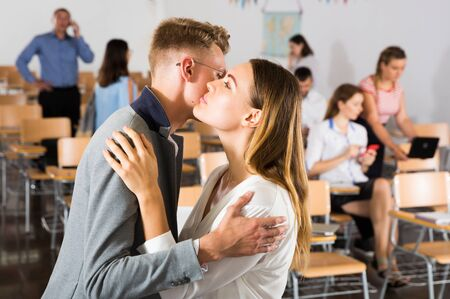 Photo pour Attractive girl and her friend kissing each other by meeting before lecture on university auditorium - image libre de droit
