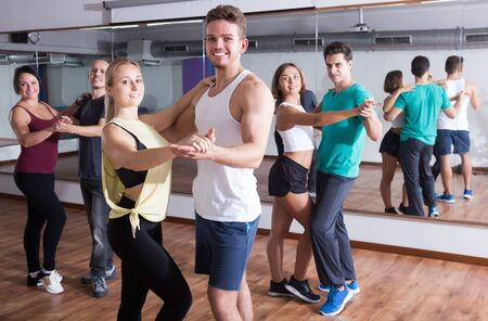Photo for Group of positive adults dancing salsa together in dance class - Royalty Free Image