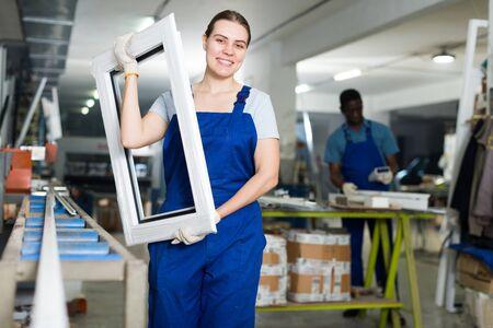 Foto für Portrait of woman worker who is standing with window frame in the pvc workshop. - Lizenzfreies Bild