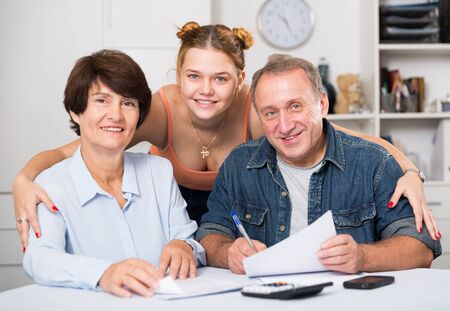 Photo pour Smiling parents are reading utility bill with their adult daughter at home. - image libre de droit