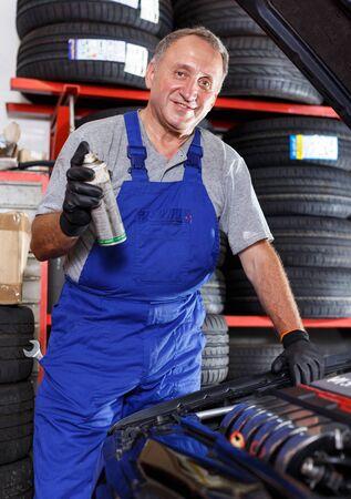 Professional mature man car mechanician repairing car in auto repair shop