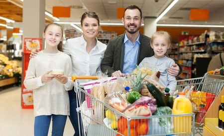 Foto für Happy family of four is standing with purchases in the supermarket - Lizenzfreies Bild