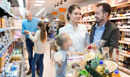 Foto für Happy cheerful positive  family is looking on shelves with products in the supermarket. - Lizenzfreies Bild