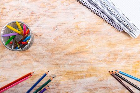 Photo pour Colored pencils and workbooks on wooden student desk with place for text - image libre de droit