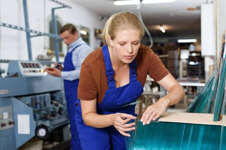 Photo pour Experienced young workwoman working with glass in industrial workshop - image libre de droit